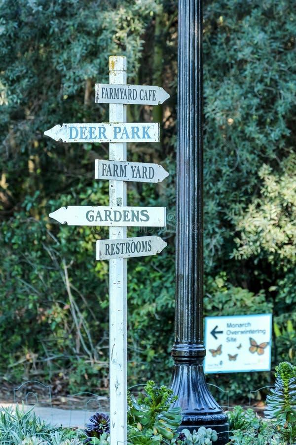 Um letreiro direcional por um poste de luz no parque imagem de stock royalty free