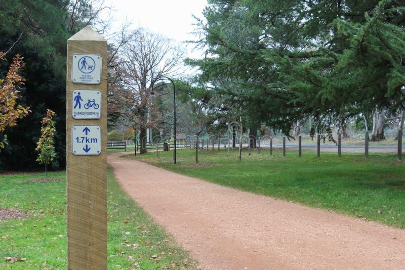Um letreiro que indica um passeio compartilhado e mantém cães na ligação em uma trilha de passeio fotografia de stock royalty free