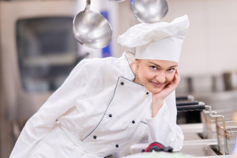 Um levantamento fêmea novo bonito do cozinheiro chefe imagem de stock