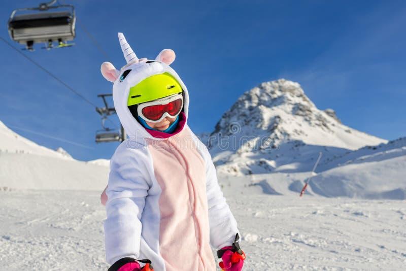Um lindo retrato de criança caucasiana, adorável e adorável, com esqui no capacete, óculos e fantasia divertida de unicórnio, que foto de stock