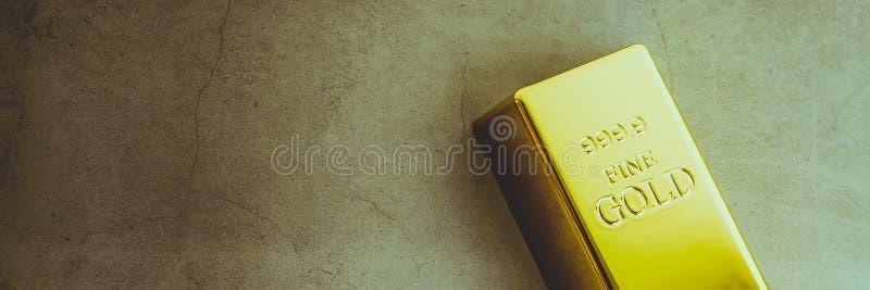 Um lingote de lingote do metal do ouro de brilhante puro situado diagonalmente em um fundo textured cinzento imagem de stock royalty free