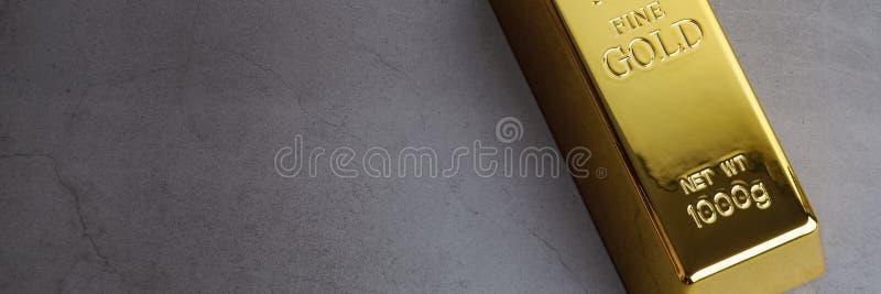 Um lingote de lingote do metal do ouro de brilhante puro situado diagonalmente em um fundo textured cinzento fotos de stock