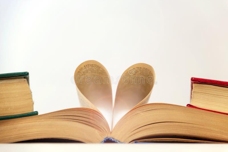 Um livro aberto com um coração das páginas, um amor da leitura e ciência fotografia de stock royalty free