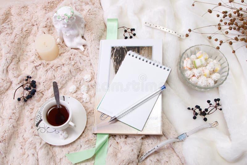 Um livro, um caderno, uma vela em um castiçal de vidro, parvarda, amendoins no açúcar, uma estatueta de um anjo feito do emplastr fotografia de stock