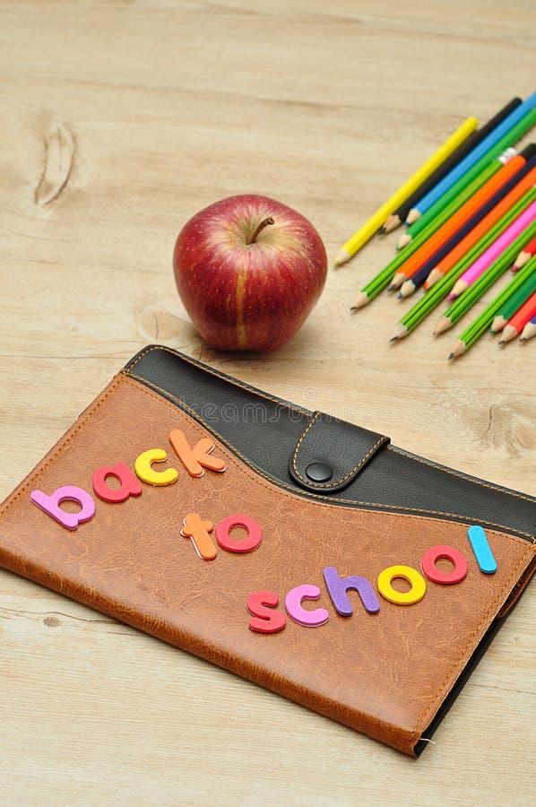 Um livro coberto de couro indicado com as palavras de volta à escola, a uma maçã e aos lápis da coloração fotografia de stock royalty free