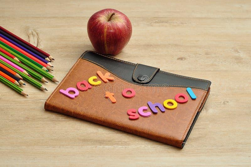 Um livro coberto de couro indicado com as palavras de volta à escola, a uma maçã e aos lápis da coloração foto de stock
