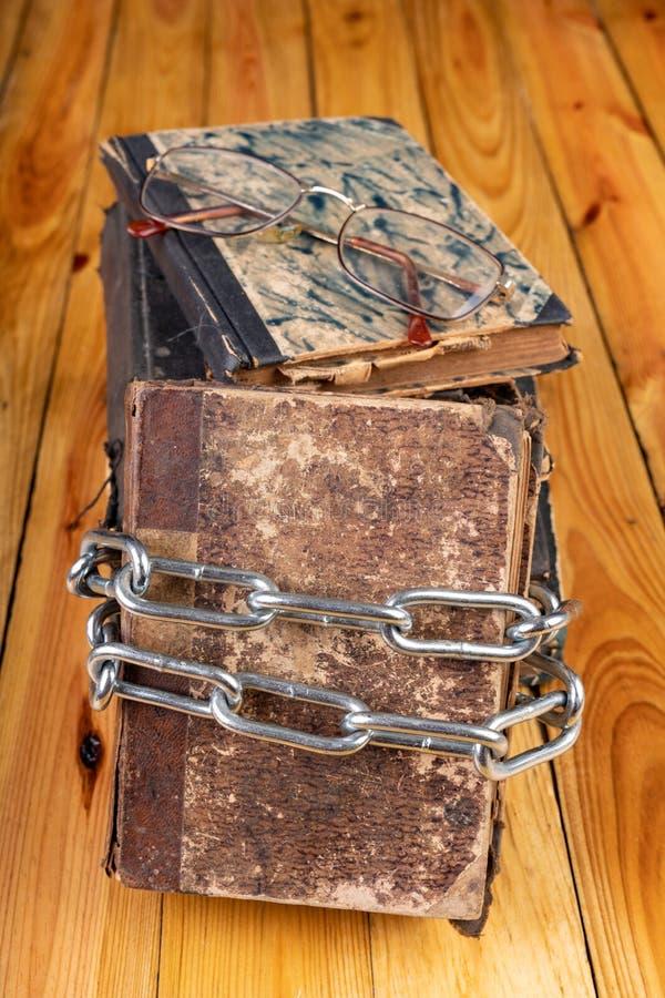Um livro velho limitado por uma corrente brilhante do metal A literatura proibida arranjou em uma tabela de madeira fotografia de stock