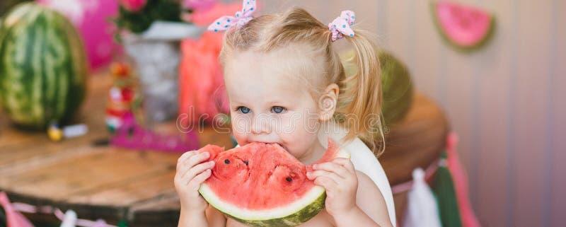 Um louro bonito da criança da menina está comendo uma parte suculenta de melancia que senta-se em uma cadeira do bebê foto de stock royalty free