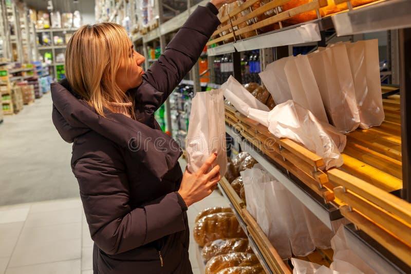 Um louro da jovem mulher em um revestimento longo escolher a compra do quando do alimento foto de stock