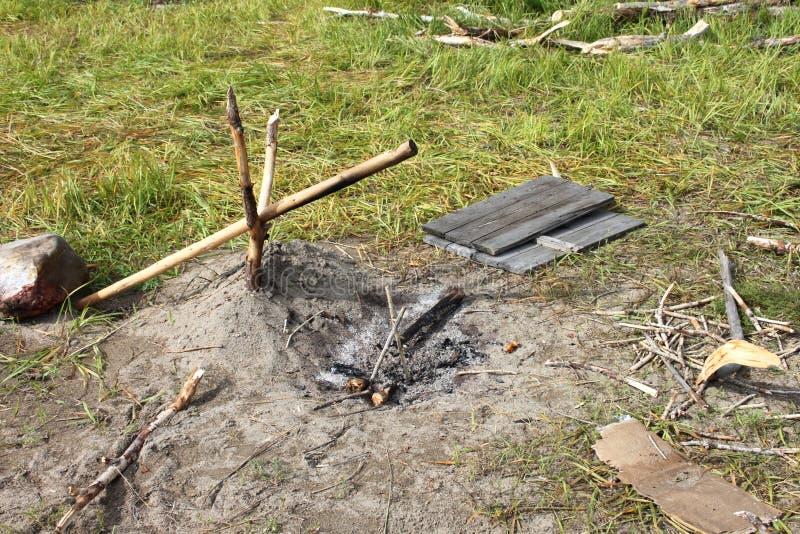 Um lugar do fogo do acampamento com o estilingue para cozinhar e os materiais para inflamar em um piquenique fotos de stock