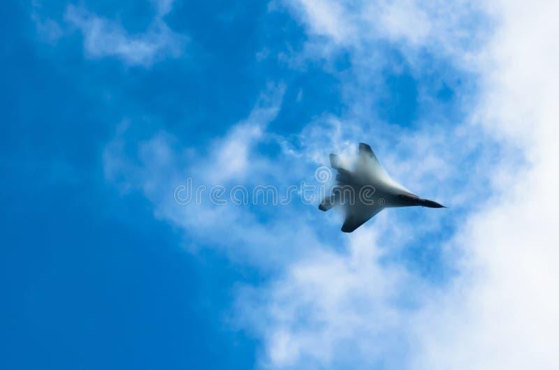 Um lutador militar alto no céu, nuvens piercing do vapor quebra fotografia de stock