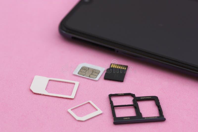 Um móbil e de memória de SIM e de SD cartões em uma superfície cor-de-rosa imagem de stock