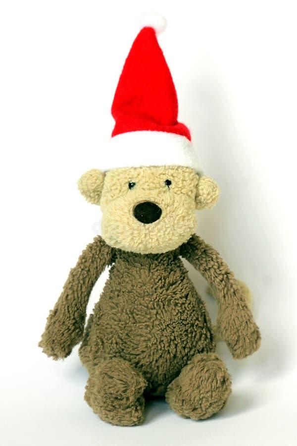 Um macaco macio do brinquedo que veste um chapéu de Santa Claus Christmas fotografia de stock