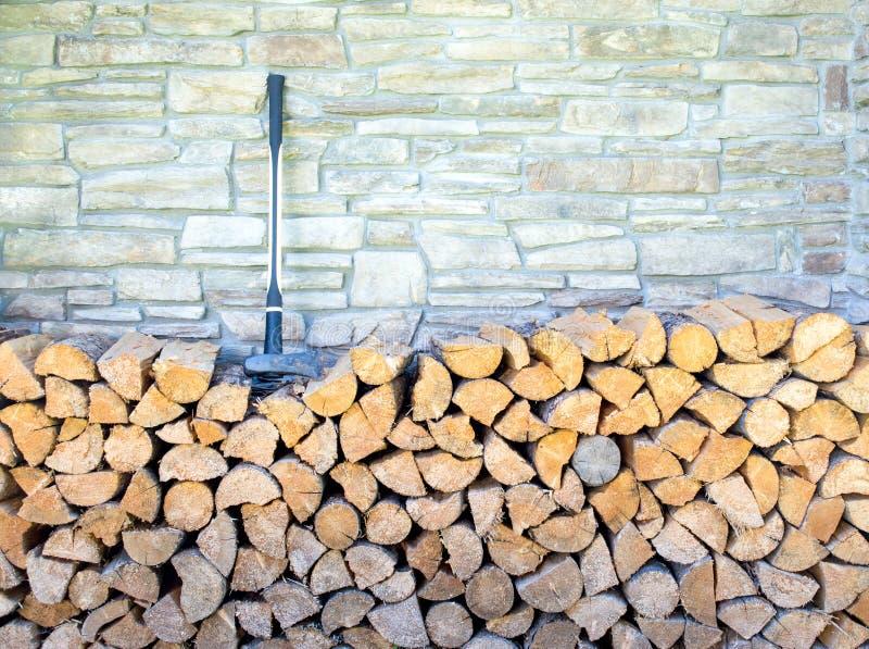 Um machado sobre uma pilha de madeira contra uma parede de pedra imagens de stock