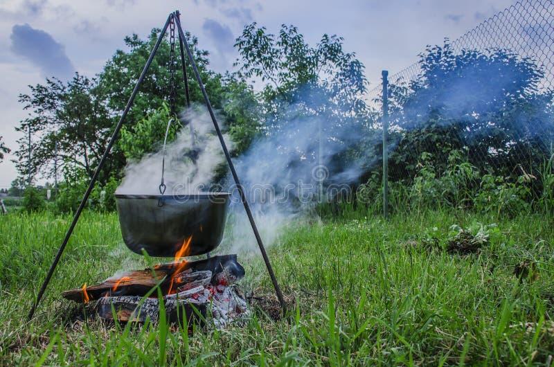 Um man' a m?o de s inflama um fogo sob uma bandeja, que esteja em um fogo imagem de stock