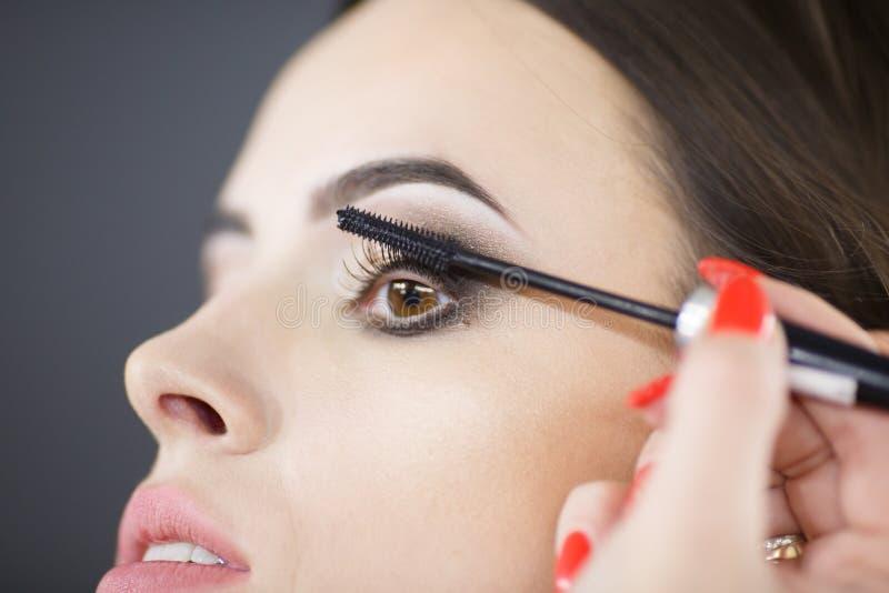 Um maquilhador bonito da moça pinta as pestanas fotografia de stock royalty free