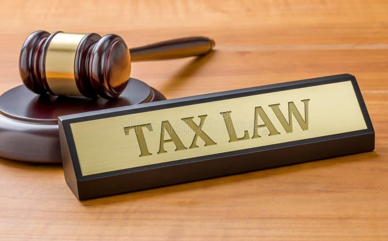 Um martelo e uma placa de nome com a lei fiscal de gravação imagens de stock