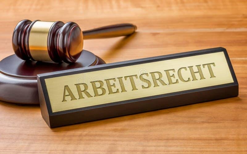 Um martelo e uma placa de nome com o Arbeitsrecht de gravação alemão foto de stock