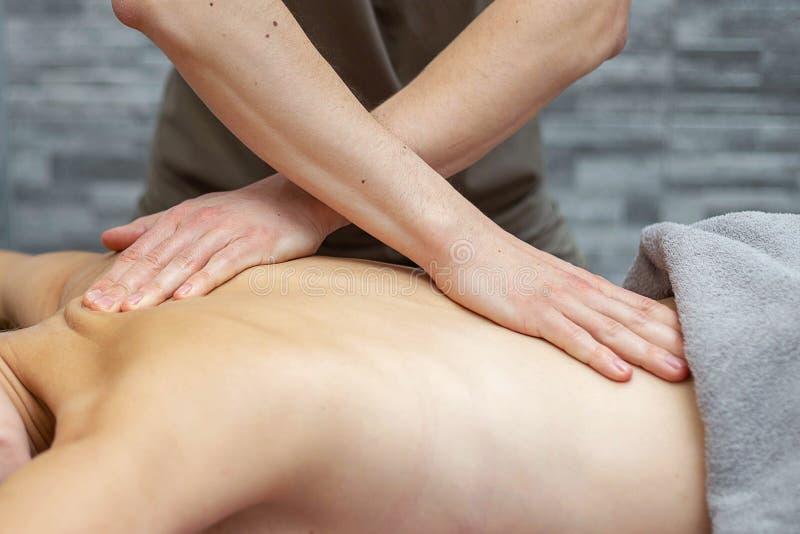 Um massagista masculino está fazendo massagens uma mulher em um salão de beleza fotografia de stock royalty free