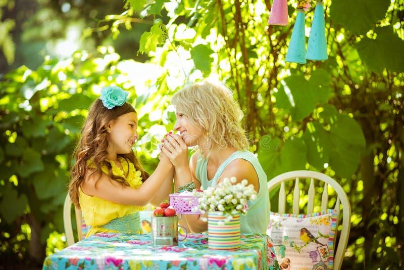 Um mather e uma filha guardam as mãos e olham entre si no jardim fotografia de stock