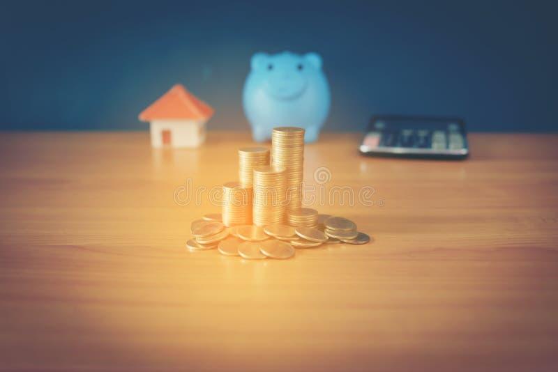 Um mealheiro posto sobre as moedas de ouro e a casa de empilhamento do quadro-negro e pulso de disparo no fundo azul do vintage,  foto de stock
