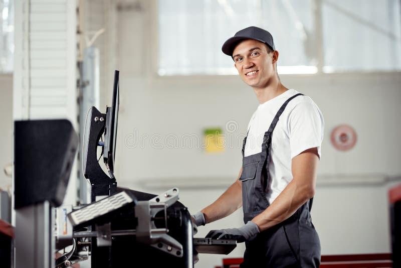 Um mecânico atrativo está sorrindo ao conduzir o diagnóstico de um carro fotografia de stock royalty free