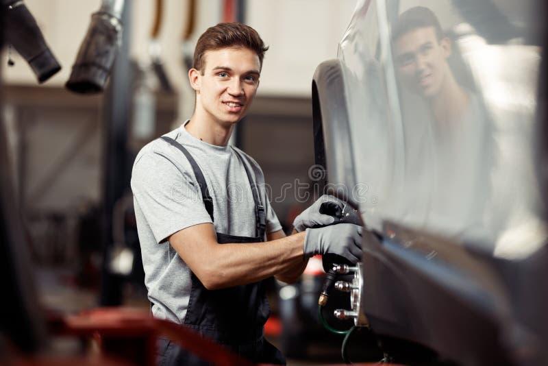 Um mecânico de carro de sorriso está fixando um carro levantado foto de stock