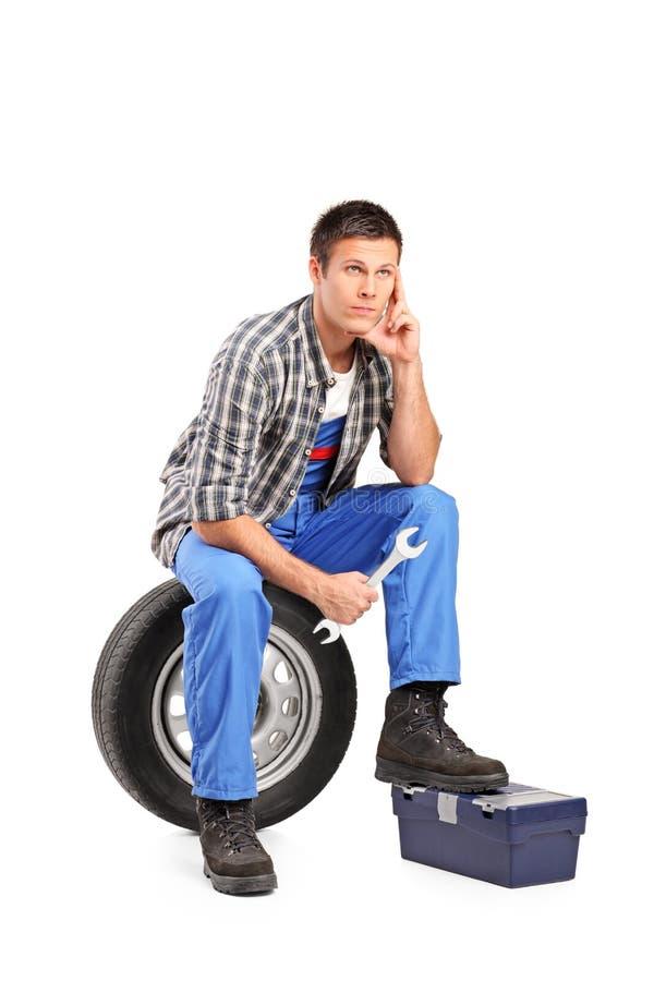 Um mecânico pensativo que senta-se em um pneu foto de stock
