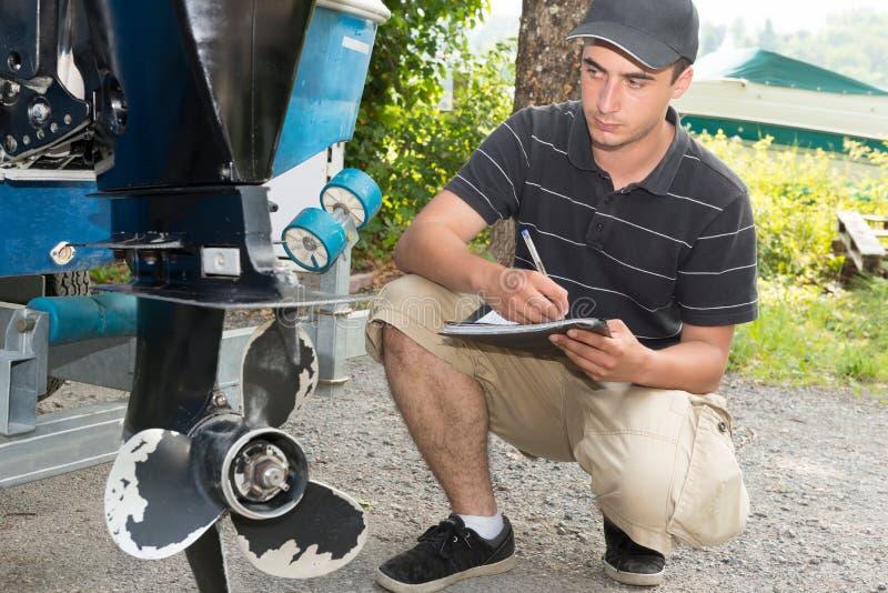 Um mecânico que verifica a hélice do barco fotos de stock