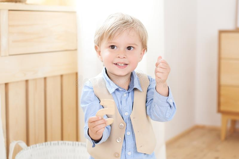 Um menino alegre e sorrindo guarda uma figura em suas mãos Crian?a no jardim de inf?ncia Retrato da crian?a masculina elegante Po imagem de stock