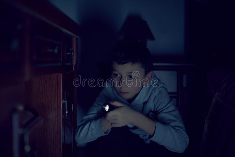Um menino assustado apenas na casa com uma lanterna elétrica em sua mão fotografia de stock