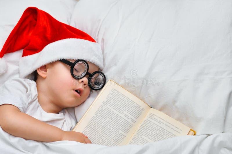 Um menino bonito da criança está dormindo em um chapéu de Santa e em uns vidros redondos com um livro velho sob uma cobertura bra imagem de stock