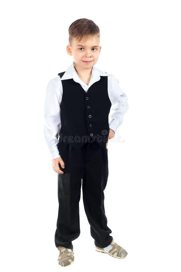 Um menino bonito em uma camisa, em uma veste e em uma calças brancas fotos de stock royalty free
