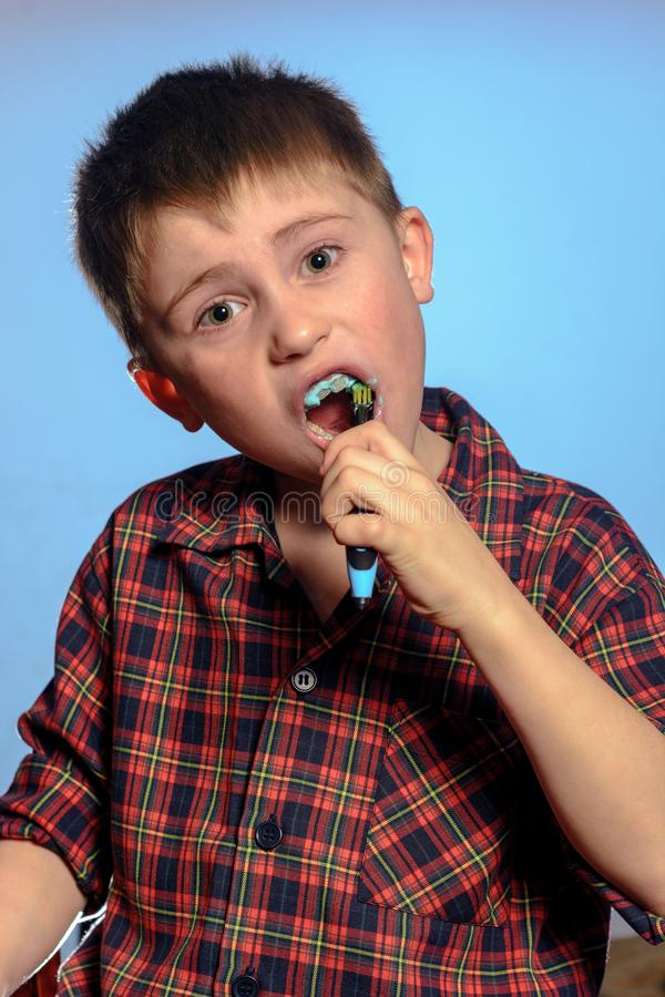 Um menino bonito no dentes das escovas dos pijamas com dentífrico antes das horas de dormir em um fundo azul imagem de stock