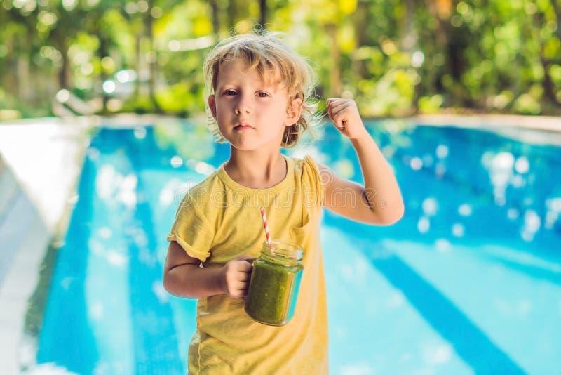 Um menino bonito que guarda uma garrafa do batido ou do suco verde está dobrando seus músculos e sorriso fotografia de stock royalty free