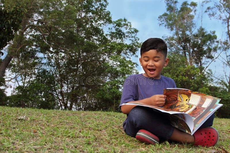 Um menino bonito que lê um livro no riso do parque imagem de stock