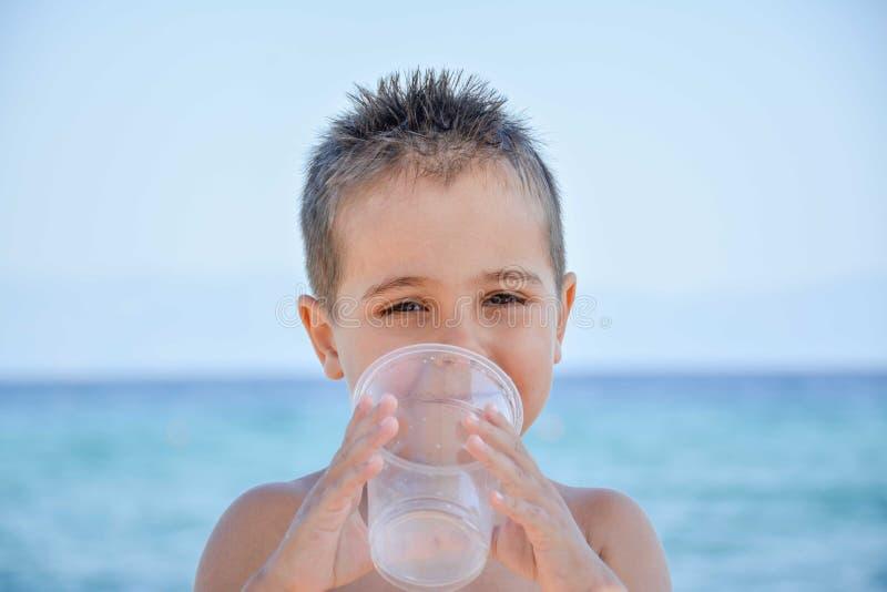 Um menino bonito que levanta na praia imagem de stock royalty free