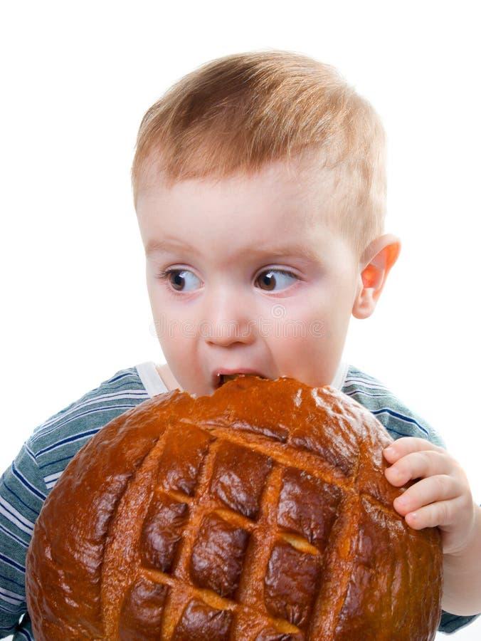 Um menino caucasiano pequeno que come um pão imagem de stock royalty free