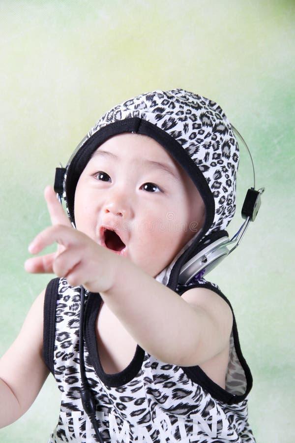 Um menino chinês bonito veste um chapéu e um earhole fotos de stock