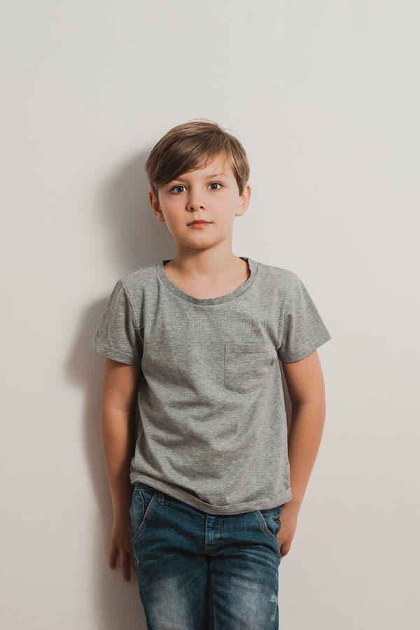 Um menino com a cara assustado pela parede branca, camisa cinzenta, calças de brim imagens de stock royalty free