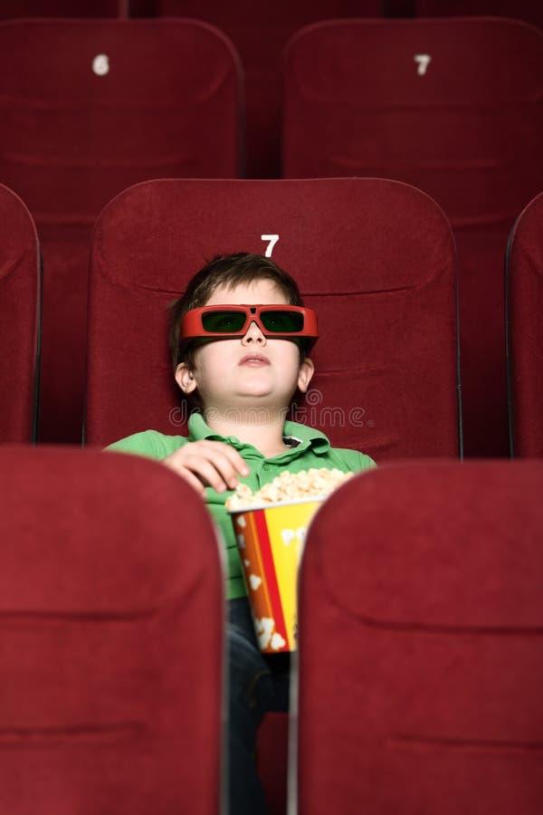 Um menino com pipoca no cinema imagens de stock royalty free