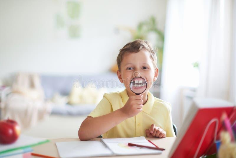 Um menino com uma lupa em seus sorrisos das mãos que mostram seus dentes ampliados retrato engraçado de uma criança do shkolnica  fotografia de stock royalty free