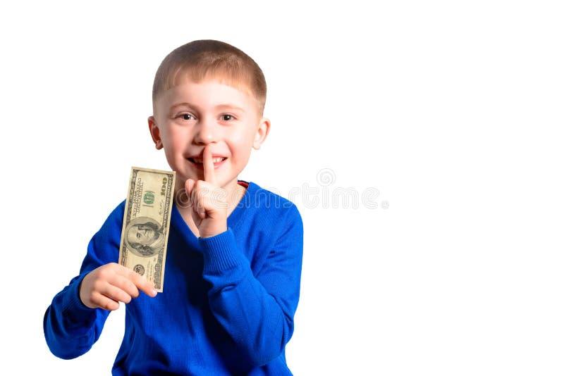 Um menino com uma nota de 100 dólares em suas mãos mostra um sinal do silêncio imagem de stock