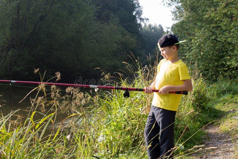 Um menino com uma vara de pesca foto de stock royalty free