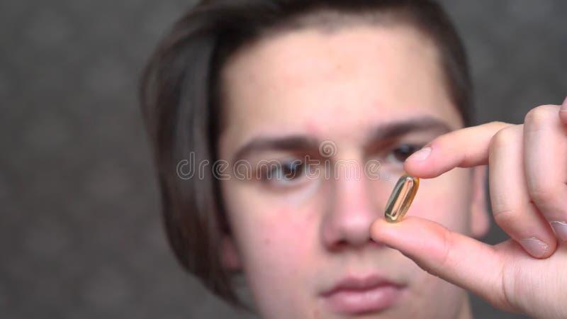 Um menino considerável um adolescente guarda uma medicina transparente, comprimidos ou vitaminas da cápsula fotos de stock royalty free