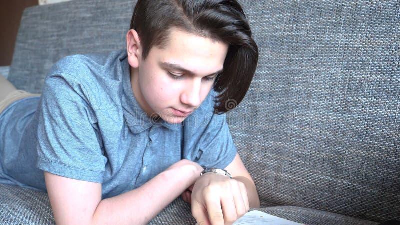 Um menino considerável um adolescente lê um livro em um sofá cinzento, olhos marrons foto de stock