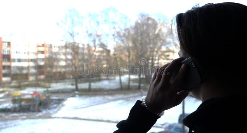 Um menino considerável um adolescente olha para fora a janela à rua com um telefone em sua mão fotografia de stock