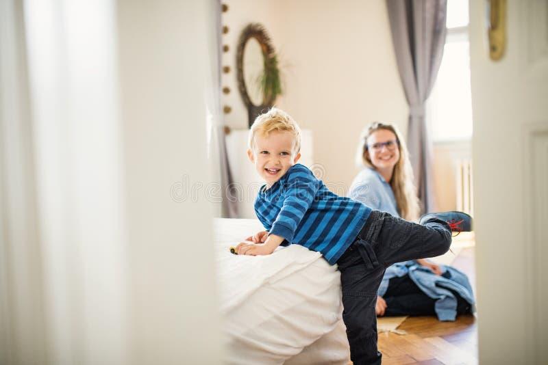 Um menino da criança com a mãe nova no interior do fundo em um quarto imagens de stock royalty free