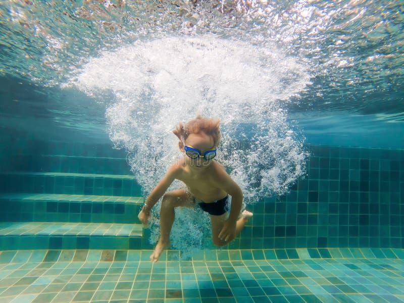 Um menino da criança está nadando debaixo d'água em uma associação, está sorrindo e está guardando a respiração, com vidros nadad imagem de stock royalty free