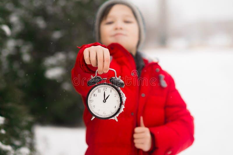 Um menino da criança guarda um despertador do pulso de disparo em suas mãos inverno d fotografia de stock